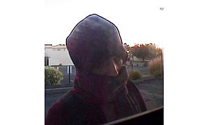 Suspect trying to hide face using stolen debit card (Kennewick police)